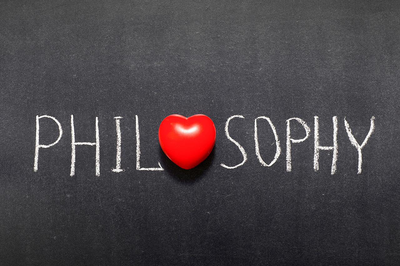 This is the word Philosophy written on a blackboard with a heart replacing the first O.